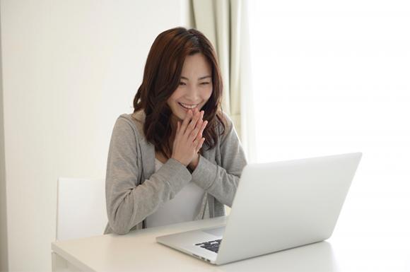 ノートパソコンの前で喜ぶ女性