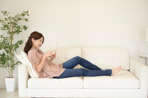 ソファの上でタブレットを操作する女性