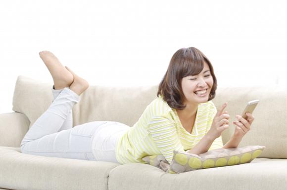 ソファの上でスマートフォンを操作する女性