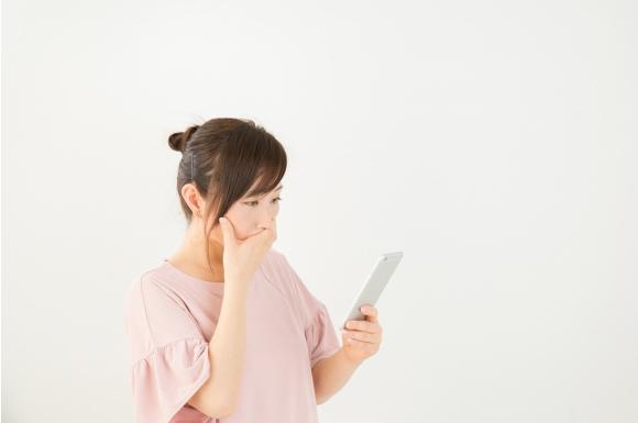 スマートフォンの前で悩む女性