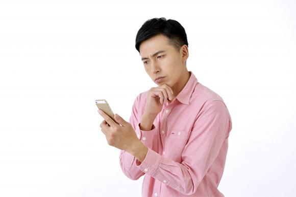 スマートフォンの前で悩む男性