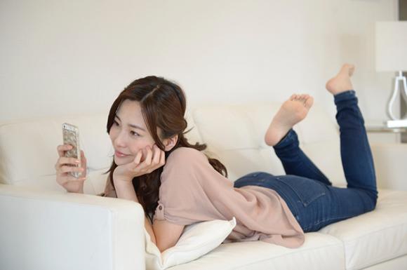 ソファーに横たわってスマートフォンを眺める女性