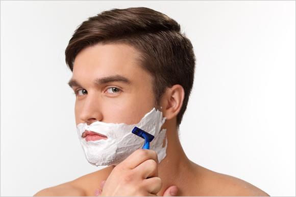 シェービングジェルを使って髭剃りする男性