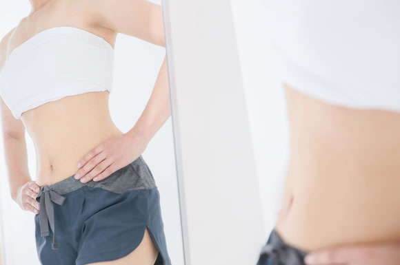 鏡にうつる痩せた女性