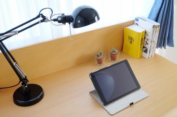 デスクライトの乗った机とタブレット