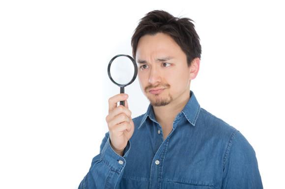 虫眼鏡でチェックする男性