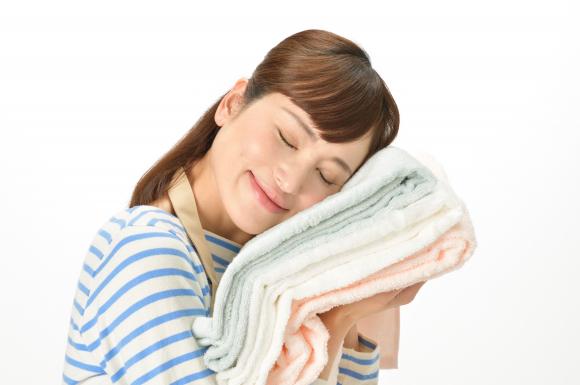 タオルに顔を当てる女性