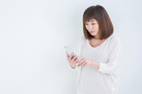 スマートフォンを操作する主婦